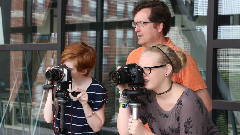 Two teenagers look through cameras while an instructor guides them.