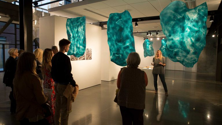 A group of people listen to an artist talking about her exhibition in the ahha gallery.