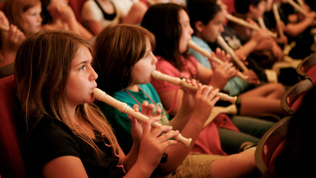 Students sit in an auditorium and play recorders.
