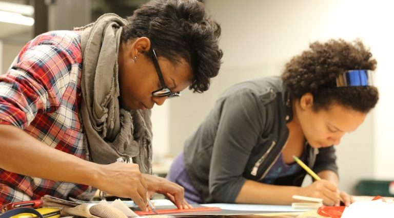 Two women bend over to focus on drafting skills for a bookmaking class.