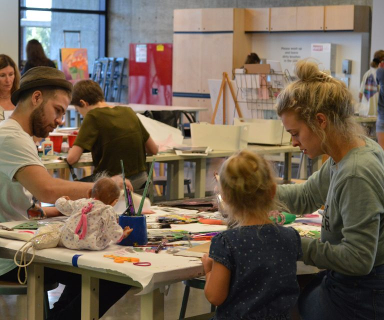 A large group of people of all ages work on art projects in the ahha Tulsa Studio.