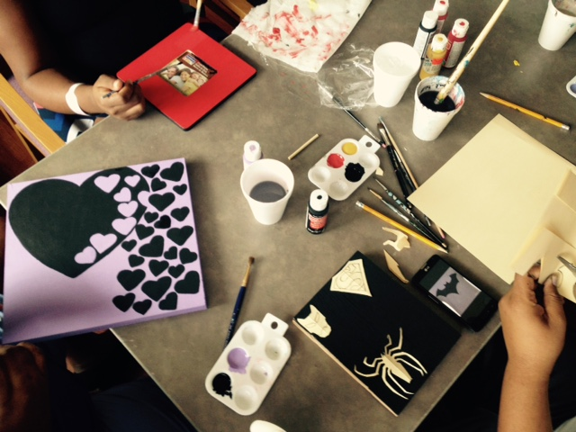 Patients sit at a table and work on art projects.
