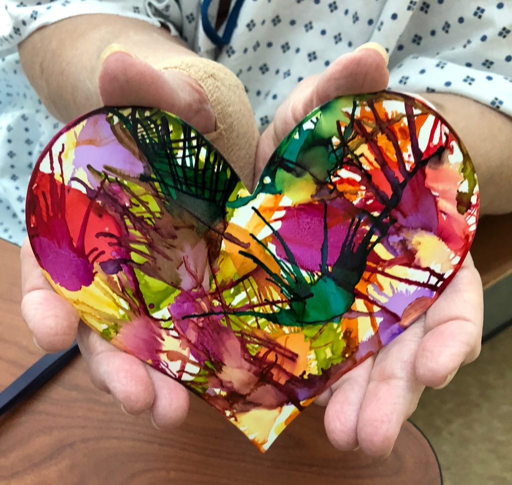 A hospital patient holds a heart she has painted.
