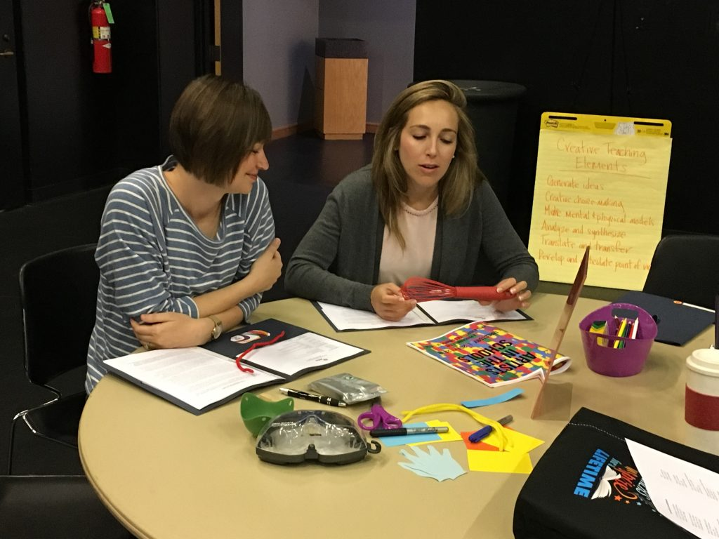 Two teachers sit at a table talking. On the table are papers, random objects, and a bucket of colored pencils and crayons.