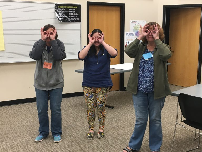 Three teachers stand and gesture with their hands like they are wearing glasses.