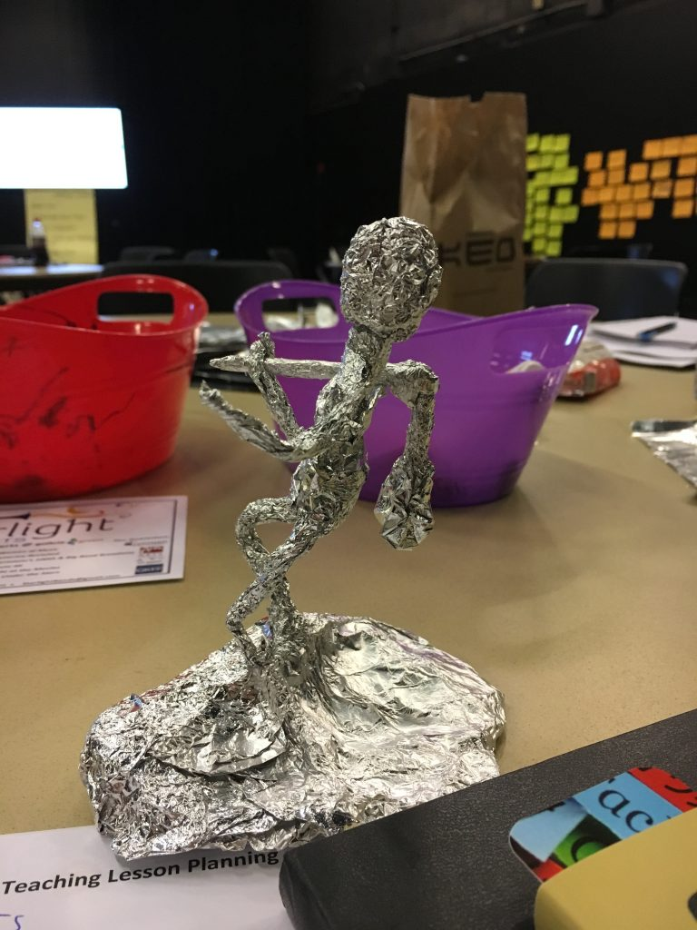 An aluminum foil sculpture of a person sits on a table.