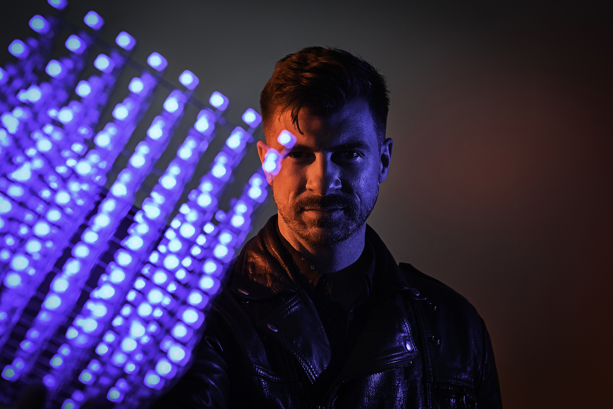 A man wearing a leather jacket is lit by the blue LED light cube he holds in his hand.