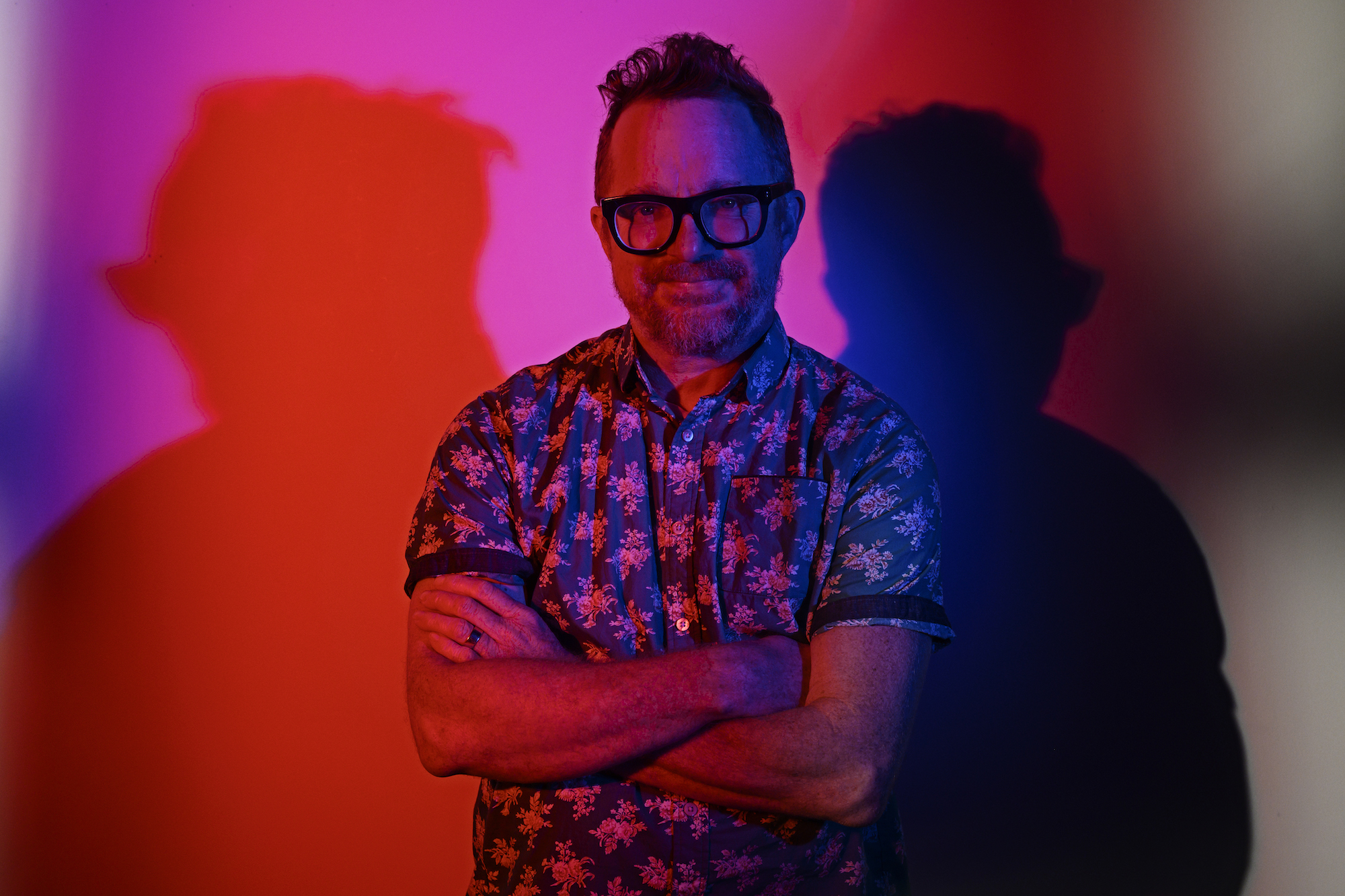 A man in a floral shirt and thick framed glasses is lit by dramatic pink lights.