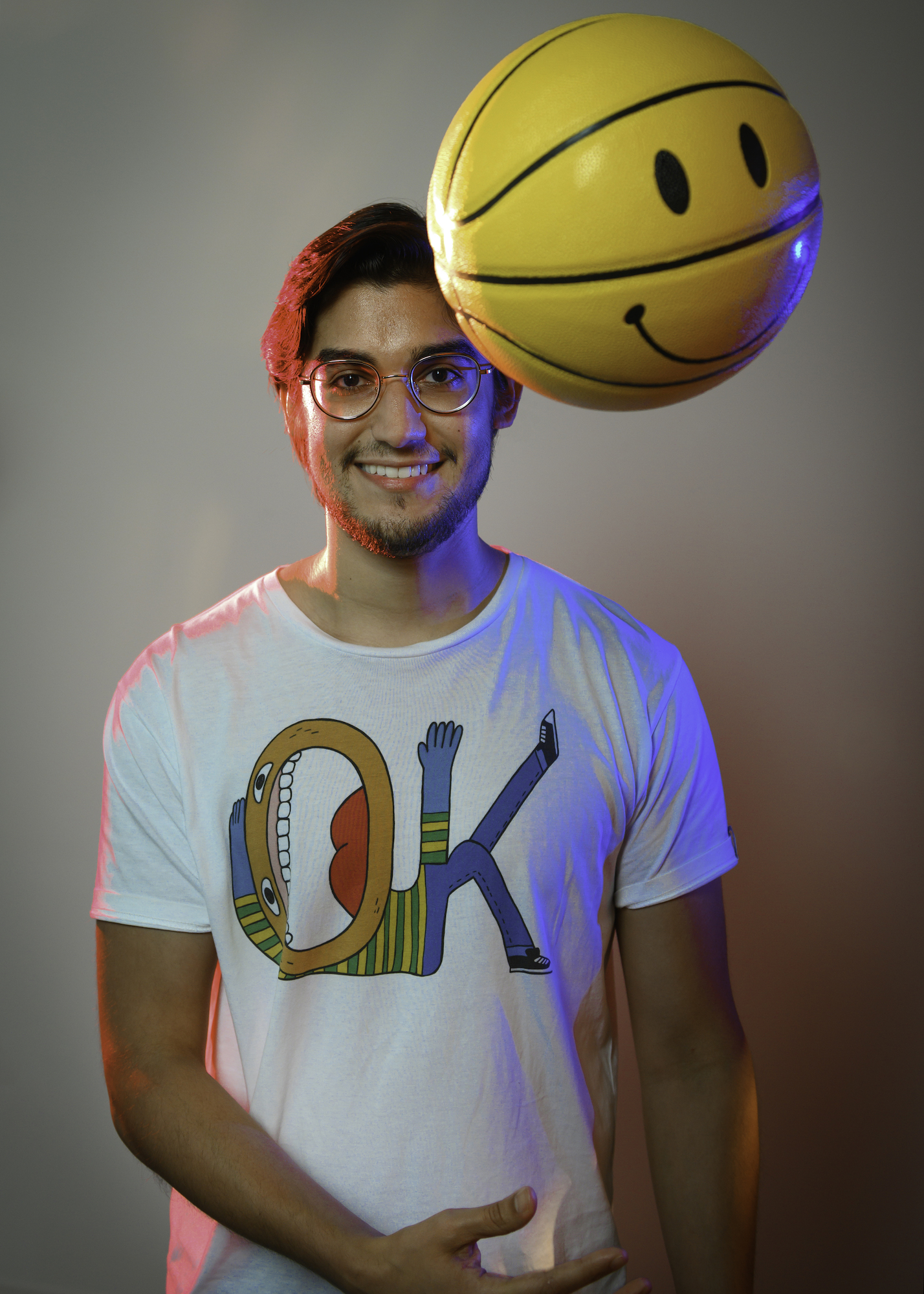 A smiling man wearing round glasses tosses a yellow basketball with a happy face on its surface.