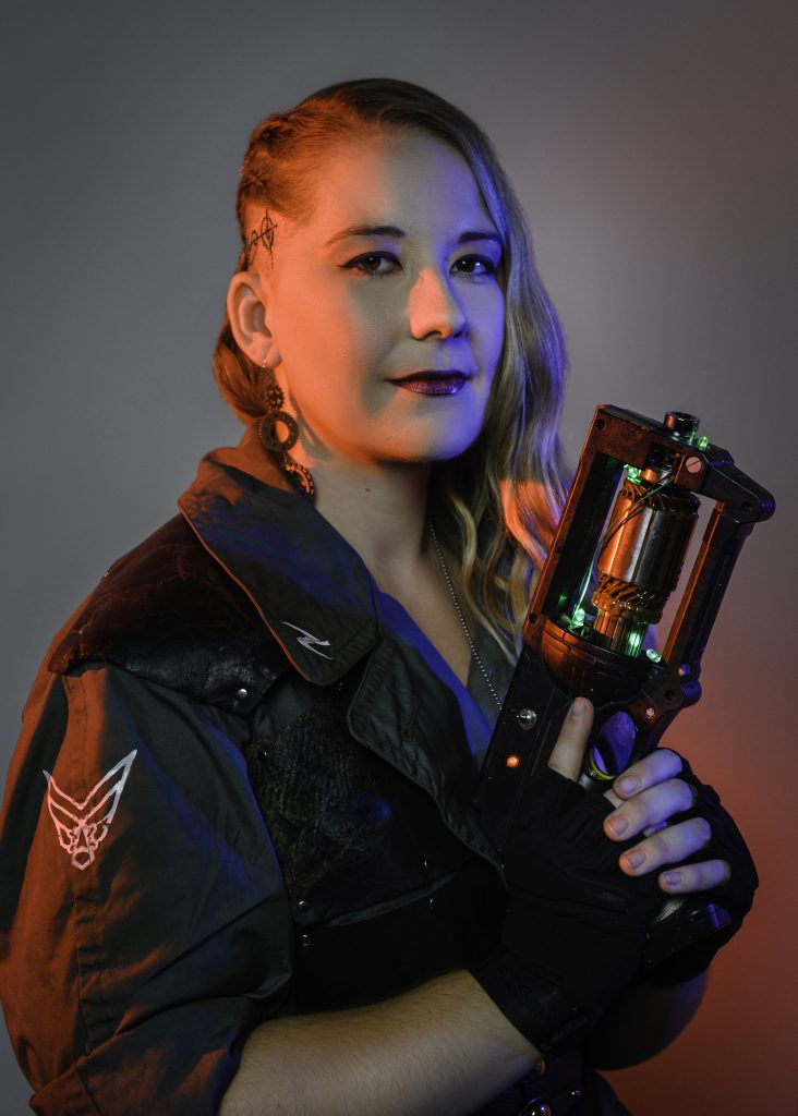 A woman wears a science-fiction themed jumpsuit and holds a futuristic faux weapon.
