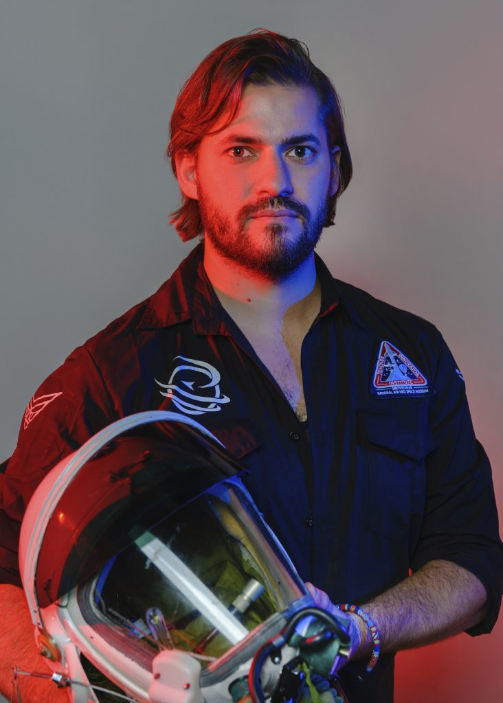 A man wears the uniform of a fictional space exploration team and holds an astronaut helmet.