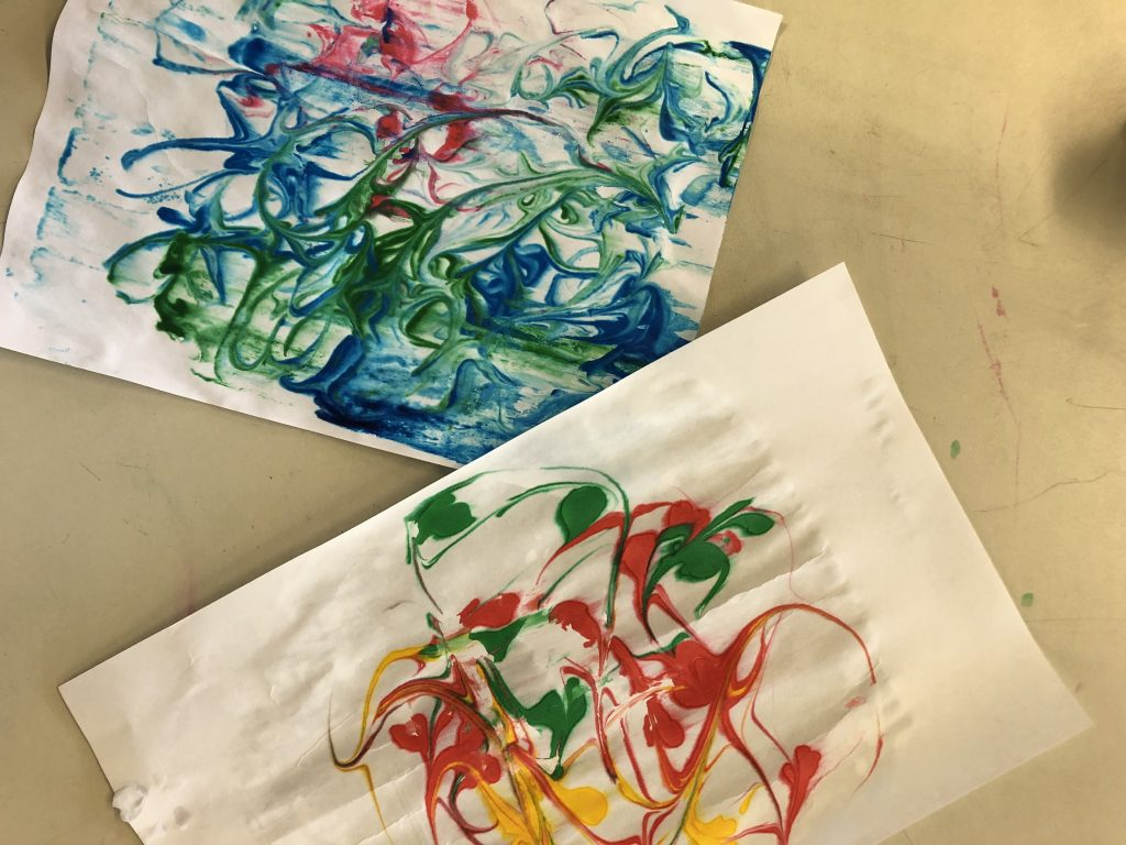 Two pieces of paper marbled with shaving cream and food coloring.