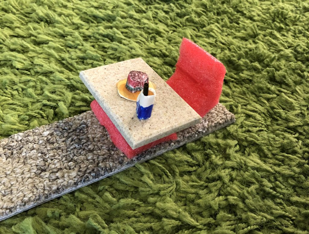 A miniature table, chair, drink, and plate with food created from random materials.