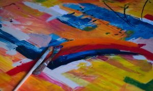 Colorful abstract work of art with paintbrushes.