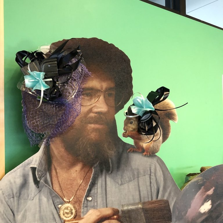 Cardboard cut out of Bob Ross with a squirrel on his shoulder, both wearing ribbons.