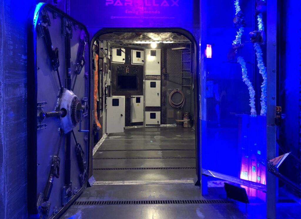 An airlock door opens into a space station module. Various cabinets and a computer can be seen in the distance.