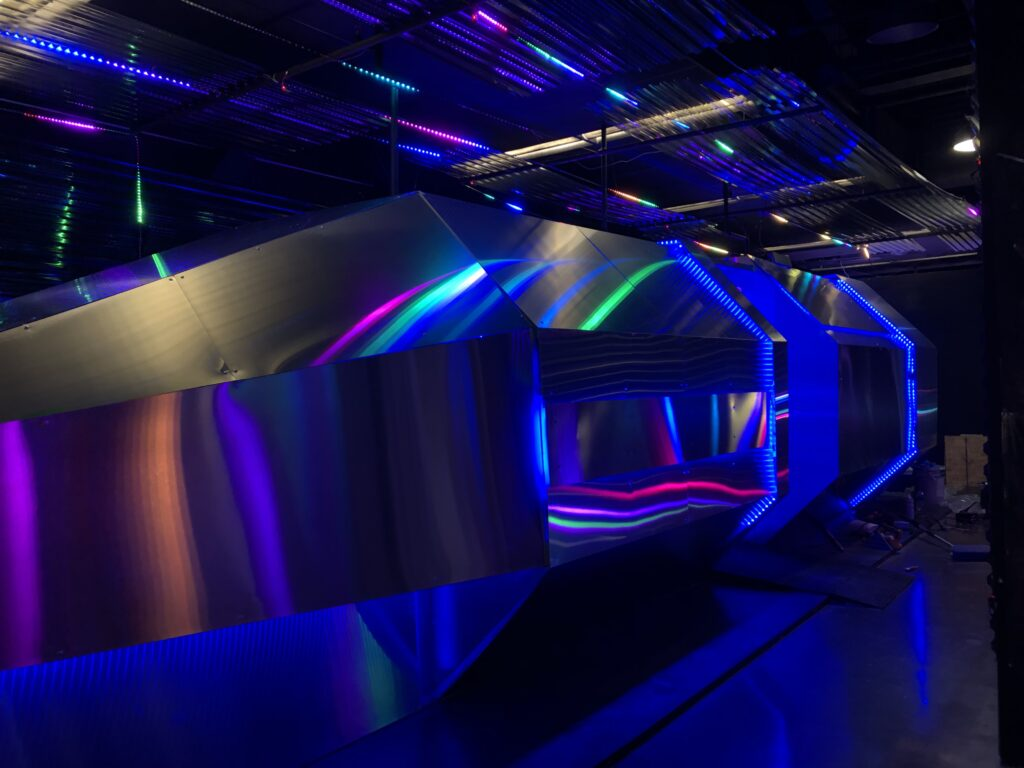The side of a large metal spaceship is lit by moving, rainbow colored LED lights. The spaceship's door can be seen in the distance.