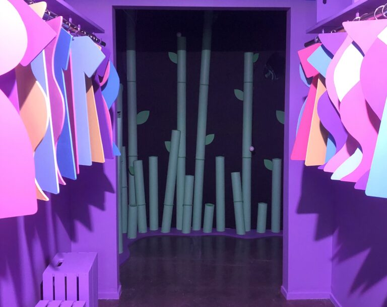 A bright purple closet with two-dimensional brightly colored clothes hanging within. Beyond the closet, there is a glimpse of a mysterious bamboo forest. Installation by Justice Gutierrez.
