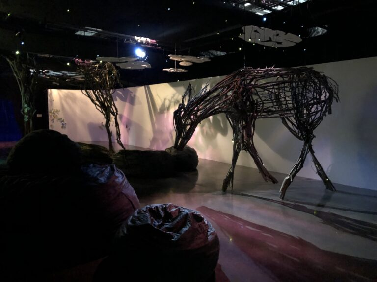 A huge deer made of tree branches stands alone in a room.