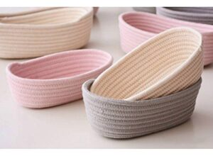 A series of pink, beige, and grey rope coiled baskets.
