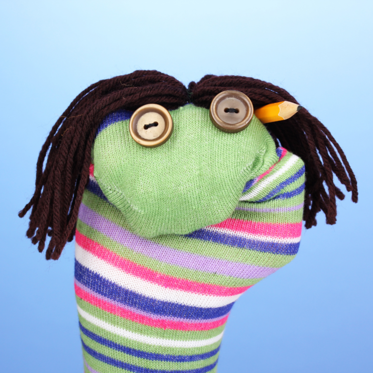 A striped sock turned into a puppet with buttons for eyes and yarn for hair.
