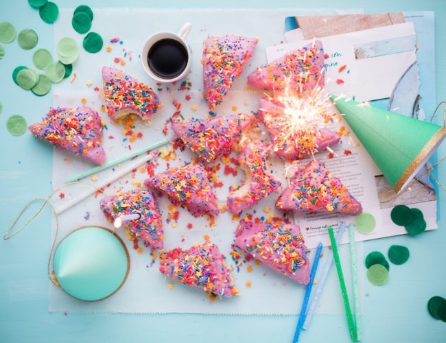Party supplies and pink, sprinkled donuts
